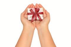De handen die van de vrouw huidige doos met rood lint houden Stock Foto