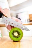 De handen die van de vrouw kiwi snijden Stock Afbeelding