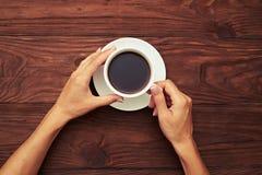 De handen die van de vrouw kop van koffie houden Stock Foto