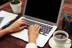 De handen die van de vrouw laptop op houten lijst met behulp van Stock Foto