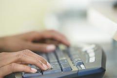 De Handen die van de vrouw op een Computertoetsenbord typen Stock Afbeeldingen