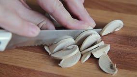 De handen die van de vrouw paddestoelchampignon snijden stock videobeelden