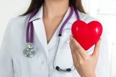 De handen die van de vrouwelijke arts rood hart houden royalty-vrije stock afbeeldingen
