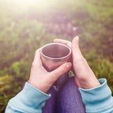 De handen die van de vrouwenreiziger kop thee houden Avontuur, reis, toerisme en het kamperen concept Royalty-vrije Stock Foto