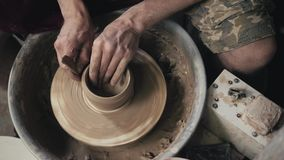 De handen die van een pottenbakker, tot een aarden kruik op de cirkel, close-up, handen op cirkel met klei leiden royalty-vrije stock fotografie