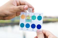 De handen die van het arbeidersgebruik reageerbuis met pH indicator het vergelijken houden royalty-vrije stock fotografie