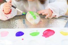 De handen die van het close-upkind door penseel en waterverf schilderen stock afbeelding