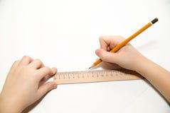 De handen die van het jonge geitje een potlood op over wit houden Stock Foto