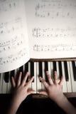 De handen die van het kind op een oude piano spelen Royalty-vrije Stock Foto's