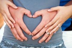 De handen die van het paar hartsymbool maken. stock foto's