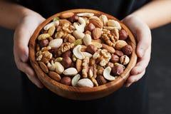 De handen die van kinderen een houten kom met gemengde noten houden Gezonde voedsel en snack Okkernoot, pistaches, amandelen, haz stock foto's