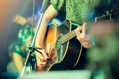 De handen die van de musicus gitaar spelen bij een levende show op stadium stock foto
