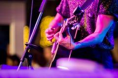 De handen die van de musicus gitaar spelen bij een levende show op stadium stock foto's