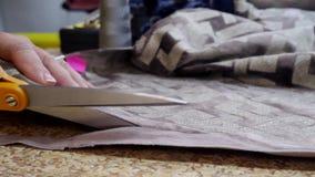 De handen die van de naaister textiel of doek snijden stock video