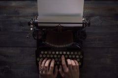 De handen die van de persoon op een uitstekende schrijfmachine schrijven royalty-vrije stock foto