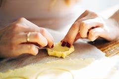 De handen die van de vrouw koekjes van ruw deeg vormen stock foto