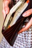 De handen die van de vrouw leerportefeuille met nieuwe Indiër 100, 200, 500, 2000 Roepiesbankbiljetten houden