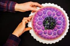 De handen die van de vrouw mousse purpere cake op de lijst houden flatlay royalty-vrije stock afbeeldingen