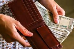 De handen die van de vrouw portefeuille met nieuwe Indische 500 Roepiesbankbiljetten houden