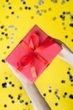 De handen die van de vrouw rode giftdoos met lint op gele achtergrond houden royalty-vrije stock foto's