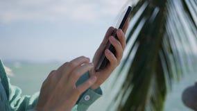De handen die van de vrouw smartphone over achtergrondoverzees en palmen gebruiken Meisje wat betreft het scherm stock video
