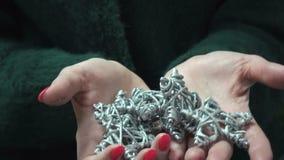De handen die van vrouwen een Kerstmisstuk speelgoed houden - sneeuwvlok stock videobeelden