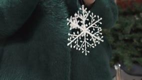 De handen die van vrouwen een Kerstmisstuk speelgoed houden - sneeuwvlok stock video