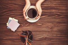 De handen die van vrouwen de stickers en de potloden van de koffiekop op houten achtergrond met exemplaar houden plaatsen op bove royalty-vrije stock afbeeldingen