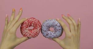 De handen die van vrouwen twee en blauw houden rood, dat donuts op roze achtergrond wordt bestrooid royalty-vrije stock foto