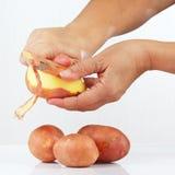 De handen die van vrouwen verse aardappels pellen royalty-vrije stock afbeeldingen