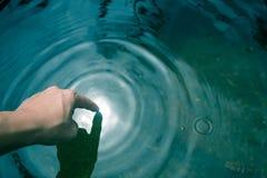 De handen dompelden in blauw water onder tot stock afbeeldingen