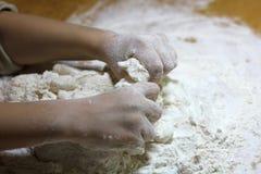 De handen en het deeg van kinderen Weinig jongen die een deeg kneden Gezond met de hand gemaakt voedselconcept bakkerijproducten, stock afbeelding
