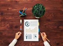 De handen en het notitieboekje van de vrouw met diagrammen Stock Fotografie