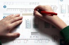 De handen en het oefenboek van het kind Stock Afbeelding