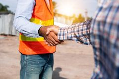 De handen en de onderhandeling van de bouwvakkerschok stock afbeeldingen