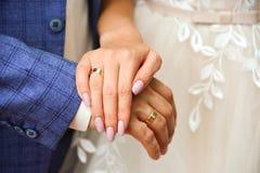 De handen en de ringen op huwelijk sluiten omhoog stock foto