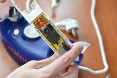De handen houden een element van een elektrisch ijzer Concept: reparatie van huishoudapparaten royalty-vrije stock afbeelding