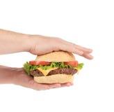 De handen houdt grote smakelijke hamburger Stock Afbeeldingen