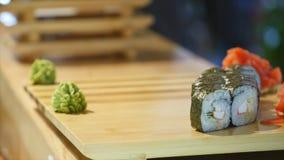De handen leggen sushi op een houten raad Een mens bereidt voedsel op de lijst voor Tijd dienende schotel stock videobeelden