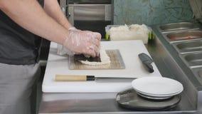 De handen maken lange sushi rollen De aantonende vaardigheid van de sushichef-kok Beroemde Japanse schotel Hoogste mening Royalty-vrije Stock Afbeeldingen