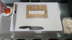 De handen maken lange sushi rollen De aantonende vaardigheid van de sushichef-kok Beroemde Japanse schotel Hoogste mening Royalty-vrije Stock Fotografie