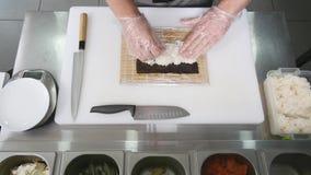 De handen maken lange sushi rollen De aantonende vaardigheid van de sushichef-kok Beroemde Japanse schotel Hoogste mening Stock Foto's