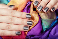 De handen met grijs manicured spijkers op kleurrijke textielachtergrond stock afbeeldingen
