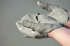 De handen met grijze modder worden behandeld, hielden open en het gezicht dat - omhoog - sluit omhoog stock afbeeldingen