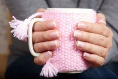 De handen met het Frans manicured spijkers houdend een theekop met gebreide dekking Royalty-vrije Stock Foto