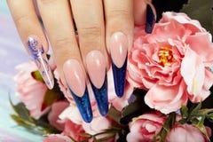 De handen met het lange kunstmatige blauwe Frans manicured spijkers en pioenbloemen stock fotografie