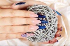De handen met het mooie lange kunstmatige blauwe Frans manicured spijkers Stock Foto