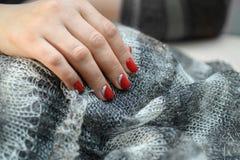 De handen met lange die kunstmatig manicured spijkers met rood nagellak worden gekleurd stock foto's