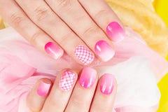 De handen met manicured spijkers met roze nagellak worden behandeld dat Royalty-vrije Stock Foto's
