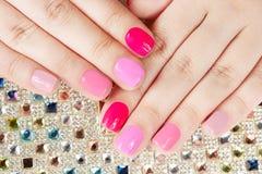 De handen met manicured spijkers op kleurrijke kristallenachtergrond Stock Fotografie